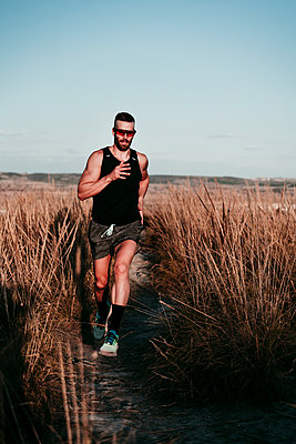 Confident male athlete running in dried grass field against sky - p300m2250913 by Eva Blanco