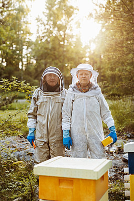 Portrait of confident beekeepers standing on field - p426m1085507f by Maskot