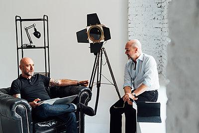 Colleagues in creative studio chatting - p429m1578587 by Eugenio Marongiu