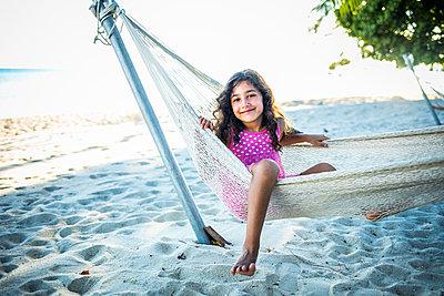 Girl in hammock on beach - p680m1511614 by Stella Mai