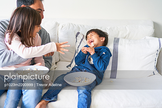 Playful family with popcorn on living room sofa - p1023m2200999 by Trevor Adeline