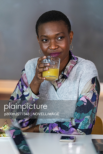 Female entrepreneur drinking juice while sitting in cafeteria - p300m2277343 by NOVELLIMAGE