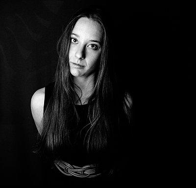 Langhaarige junge Frau blickt in die Kamera (Schwarz-Weiß) - p1180m1119825 von chillagano