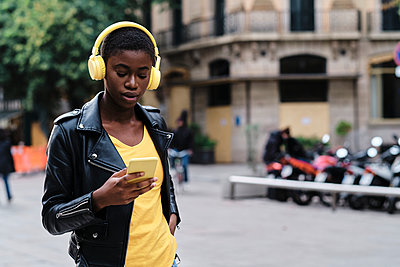 Young woman wearing headphones using mobile phone while standing in city - p300m2250166 by Alvaro Gonzalez
