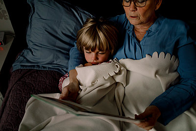 High angle view of grandmother reading story book for grandson on bed at home - p426m2195347 by Maskot