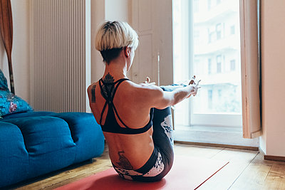 Woman practising yoga at home - p429m2033188 by Eugenio Marongiu
