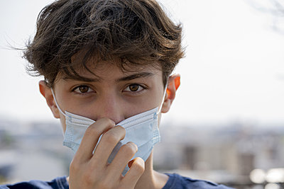 Close up of teenage boy wearing blue surgical mask outdoors - p623m2186246 by Frederic Cirou