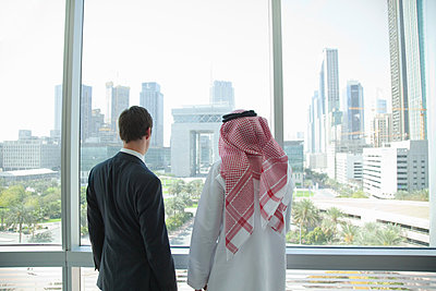 Western and middle eastern businessmen by window of dubai office - p9244775f by Image Source