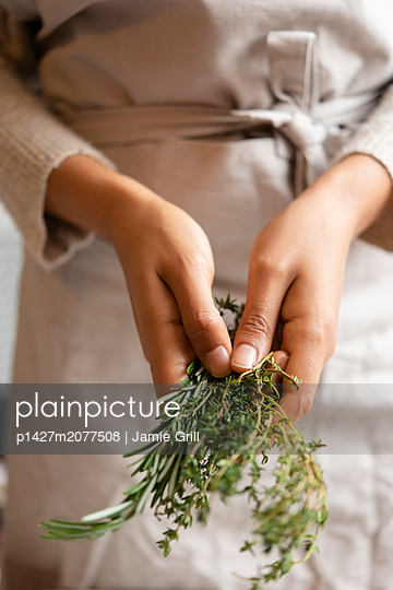 Hands of young woman holding rosemary - p1427m2077508 by Jamie Grill