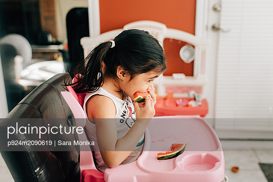 Girl in high chair eating water melon, side view - p924m2090619 by Sara Monika