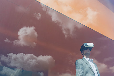 Businessman using virtual reality simulator glasses at window with reflection of clouds - p1023m1519862 by Martin Barraud