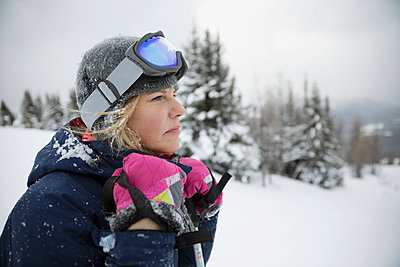 Thoughtful female skier looking away in snow - p1192m1546620 by Hero Images