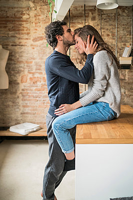Young man kissing girlfriend on forehead at kitchen bench - p429m1447863 by Arno Images