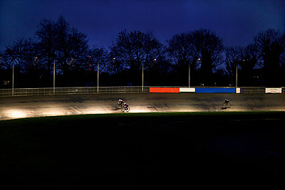 Young adult cyclists racing on velodrome track - p429m928890f by Dark Horse