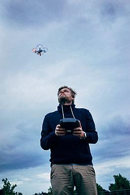 Mann steuert eine Drohne - p819m1042470 von Kniel Mess