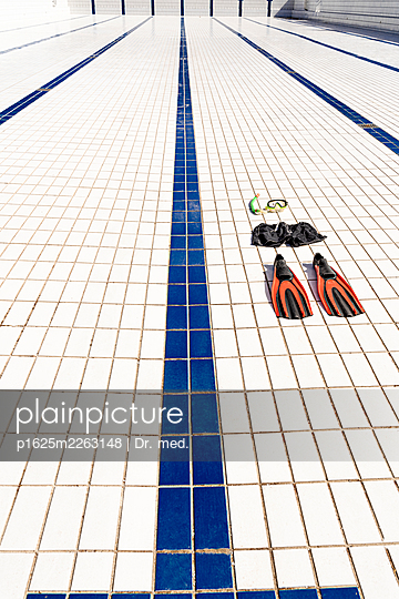 Flippers and snorkel on floor tiles in empty pool - p1625m2263148 by Dr. med.