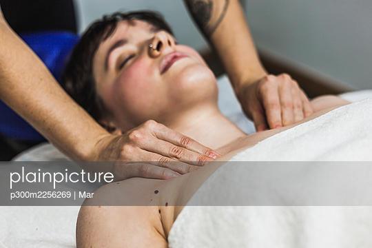 Hands of female chiropractor massaging shoulders of young woman - p300m2256269 by Mar