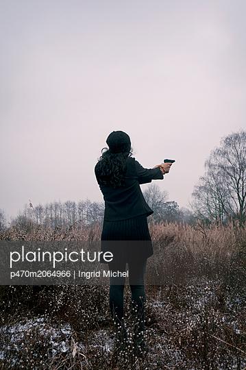 Woman holding a pistol - p470m2064966 by Ingrid Michel