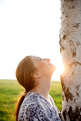 Smiling young woman looking up on a tree trunk enjoying nature - p300m2277269 by Jean Schwarz