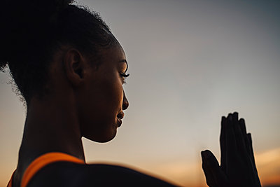 Young sportswoman practicing yoga against sky during sunset - p426m2270862 by Maskot