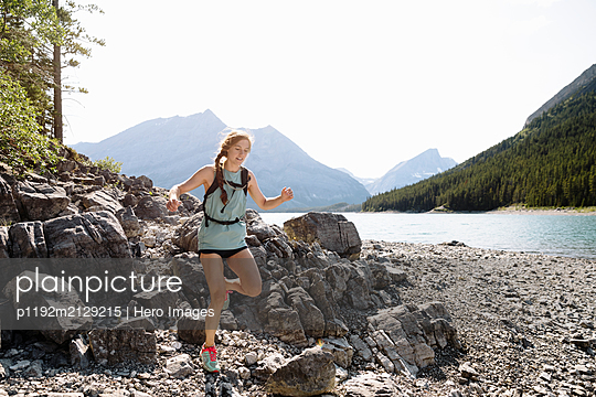 Woman running over rocks at sunny lakeside - p1192m2129215 by Hero Images