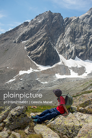 Young boy having a break while hiking in mountain - p1216m2184951 by Céleste Manet