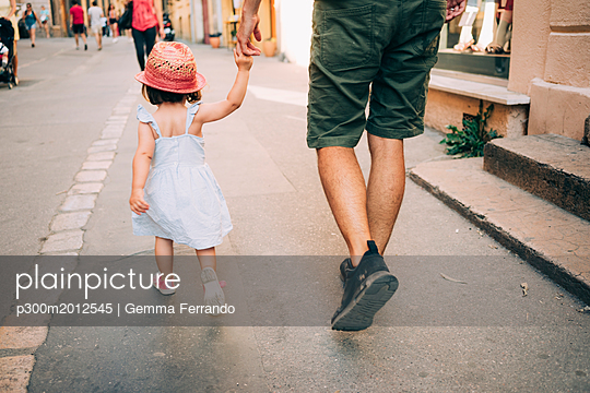 France, Aix-en-Provence, toddler girl and father walking hand in hand in the city - p300m2012545 by Gemma Ferrando