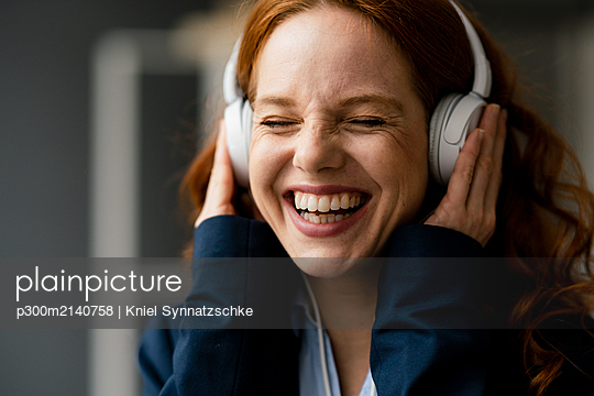 Portrait of laughing redheaded businesswoman listening music with white headphones - p300m2140758 by Kniel Synnatzschke