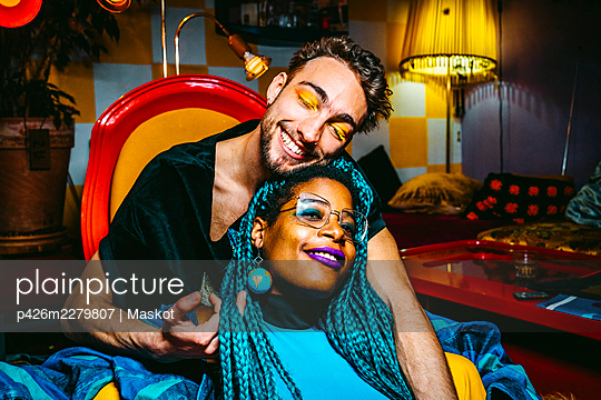Smiling braided hair woman sitting with male friend in living room - p426m2279807 by Maskot