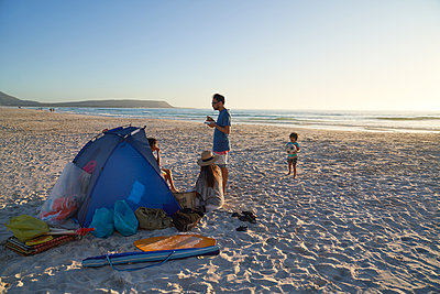 Family relaxing and playing at tent on ocean beach, Cape Town - p1023m2200880 by Trevor Adeline