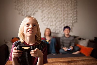 Boy playing video game with friends at home - p1166m1142640 by Cavan Images