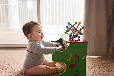 Side view of curious baby boy playing toy piano at home - p1166m1568974 by Cavan Images