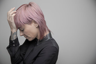 Beautiful non-binary gender person with pink hair and head in hands - p1192m2066232 by Hero Images