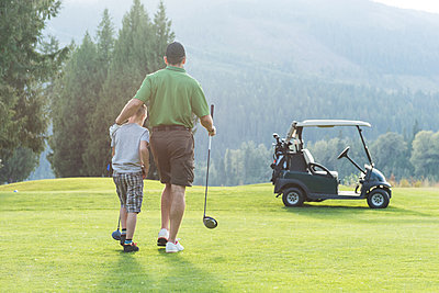 Rear view of father and son walking with golf club in the course - p1315m1565187 by Wavebreak