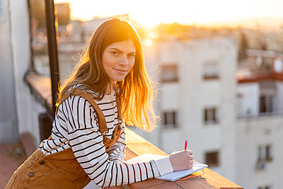 Portrait of young woman taking notes on roof terrace at sunset - p300m2083051 by VITTA GALLERY