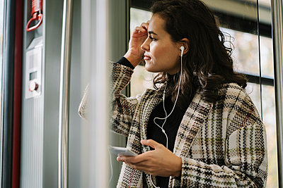 Young woman with earphones and smartphone on a subway - p300m2143462 von Hernandez and Sorokina
