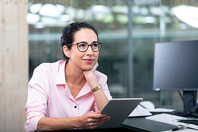 Thoughtful businesswoman with digital tablet at office - p300m2266014 by Florian Küttler