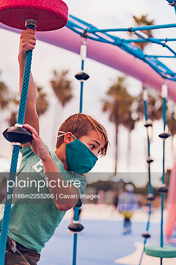 Boy wearing a mask playing alone at a playground - hanging. - p1166m2255266 by Cavan Images