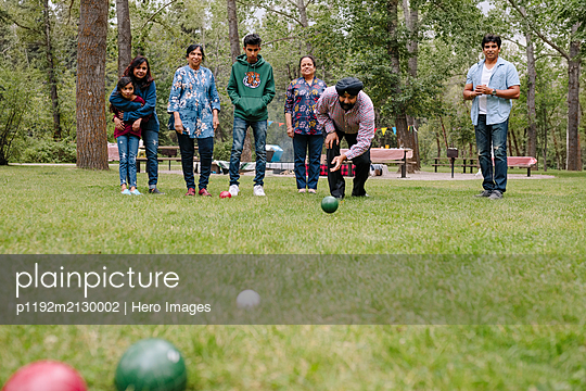 Indian family playing bocce in park - p1192m2130002 by Hero Images