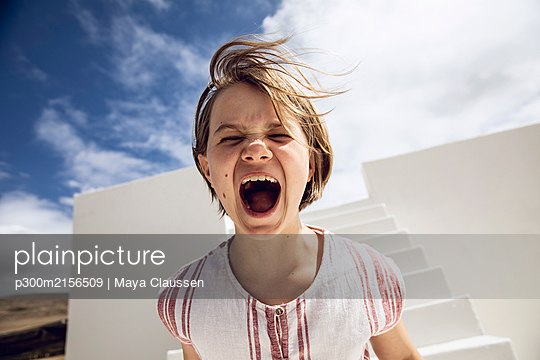 Girl with windswept hair, screaming out loud - p300m2156509 by Maya Claussen