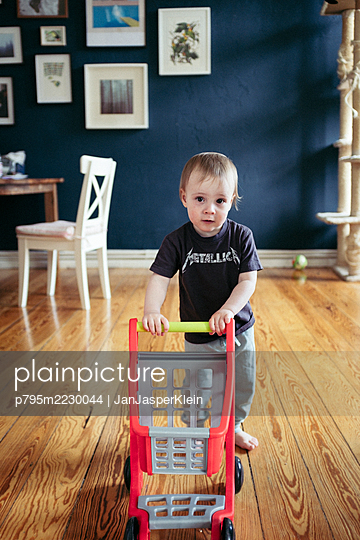 Toddler pushing toy shopping cart at home - p795m2230044 by JanJasperKlein