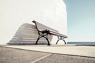 Verlassene Bank an weisser Wand vor dem Atlantik - p1162m1516857 von Ralf Wilken