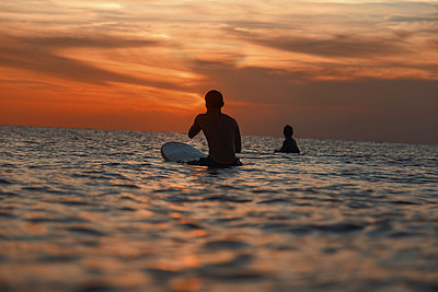 Two surfers in ocean at sunset - p1166m2137252 by Cavan Images