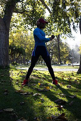 Dark-skinned man in sportswear warms up - p1640m2260988 by Holly & John