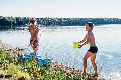 Children splashing with water at lakeshore - p300m1499423 by Jana Mänz