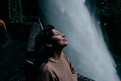 Woman with eyes closed relaxing at waterfall - p300m2274488 by MORNINGVIEW AGENCY