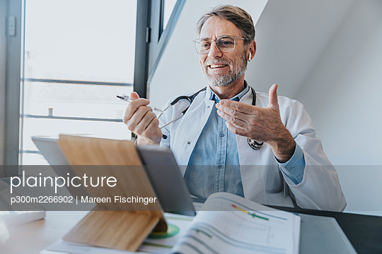 Smiling doctor discussing on video call over digital tablet while sitting at clinic - p300m2266902 by Mareen Fischinger