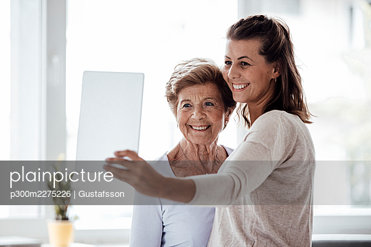 Happy woman taking selfie with grandmother through digital tablet at home - p300m2275226 by Gustafsson