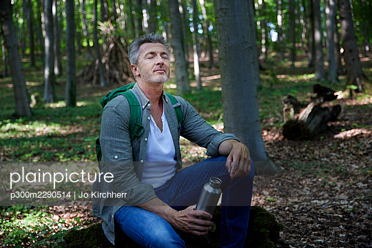 Man holding water bottle while sitting in forest - p300m2290514 by Jo Kirchherr