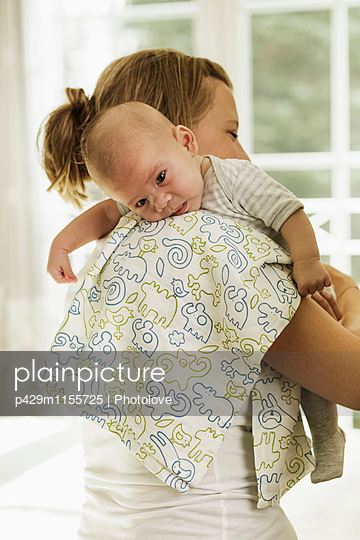 Mother burping baby son whilst carrying him on her shoulder - p429m1155725 by Photolove
